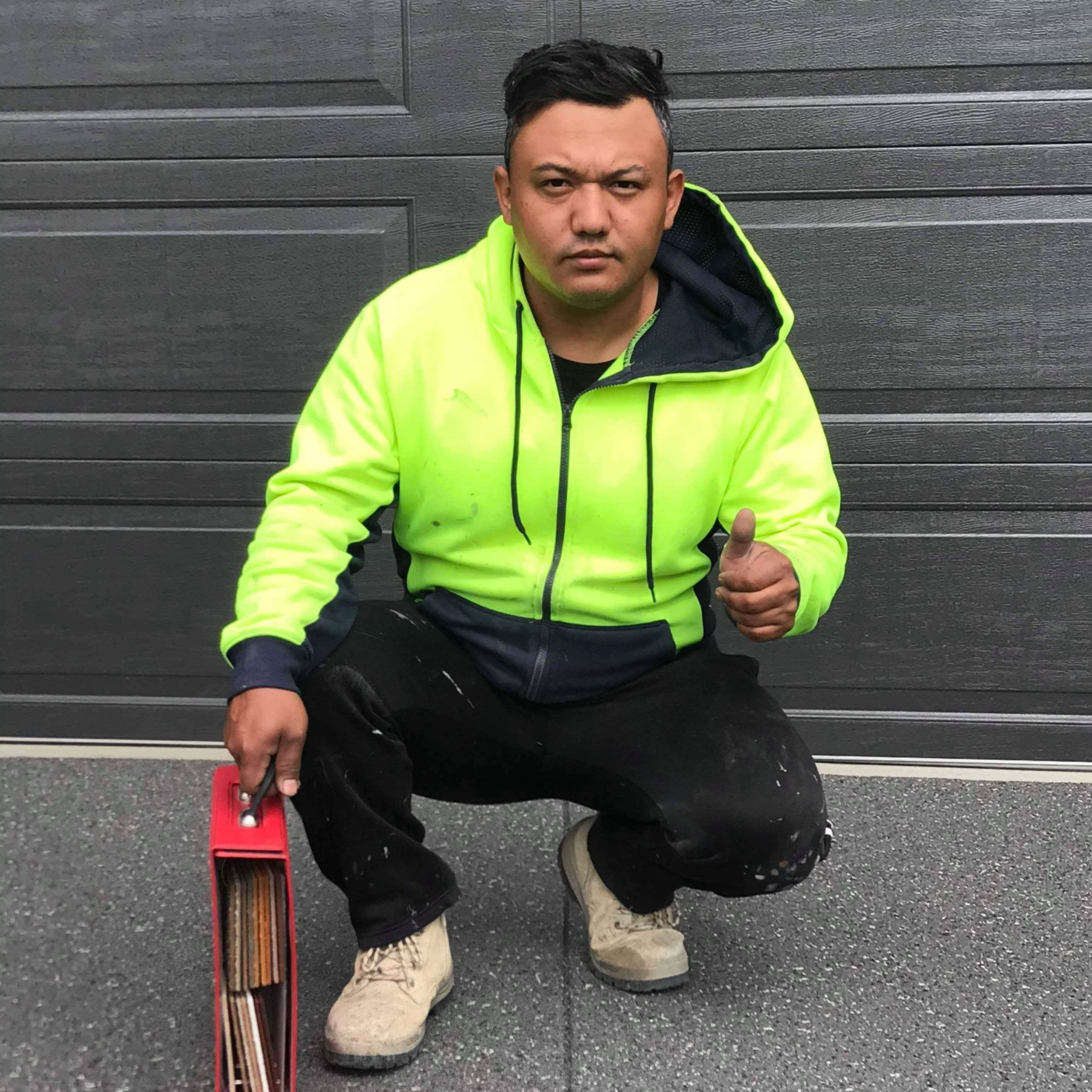Photo of Ali Jasonn, Co-owner of Home Concrete Transformers and flooring expert, kneeling and wearing hi-vis, holding a flooring sample book and giving a thumbs up.